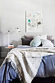 Woolen blanket over cozy bed with lots of different pillows