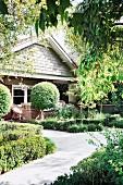 Weg durch den üppig grünen Vorgarten zum Haus