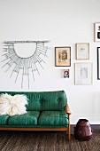 Green retro sofa with fur cushions in front of the picture wall