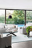Summery living room with window front to the garden with pool