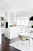 Bright, open kitchen and dining room with white furniture