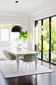 Bright dining room with white furniture and black light