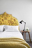 Stool next to the bed with a yellow upholstered headboard