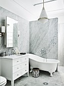 Vanity unit and free-standing tub, in elegant bathroom with marble paneling