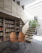 Designer chairs in front of bookcase in concrete house