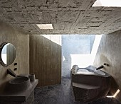 Béton brut in bathroom; bathtub and sink made from moulded concrete