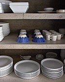 White crockery and blue-patterned cups on concrete shelves