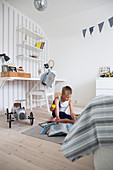 Boy playing in white and blue bedroom