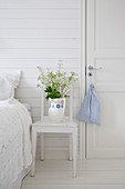 Flowers in old jug on chair used as bedside table