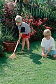 Children rake grass clipping together