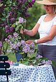 Woman arranges bouquet of lilac