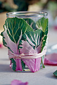 Lantern glass wrapped with brassica and bast leaves