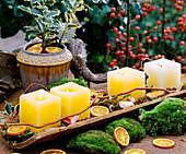 Brick rain gutter with 4 candles, orange slices, Ilex holly, moss, berries
