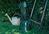 Still life old zinc watering can, bell jar and floor fan at watering hole