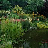 Large flowering perennial border at garden pond