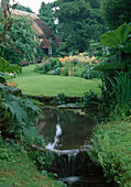 Creek in the country house garden, view over the lawn to the perennial border
