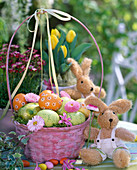 Pink handle basket with Easter eggs and flowers