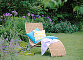 Basket lounger before blue bed with Iris sibirica (meadow iris)