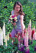 Young woman with floral bouqut snout Lupinus (lupine)