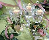 Wine glasses with floating candles decorated with paeonia (peony)