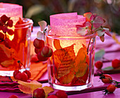 Glass windlights filled with autumn leaves, transparent paper