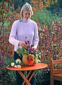 Young woman puts autumn bouquet in cucurbita (pumpkin) as a vase