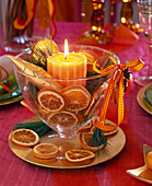 Honey-colored candle in glass cup filled with orange slices