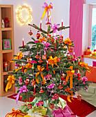 Abies nordmanniana (Nordmanntanne) als Weihnachtsbaum mit roten Kerzen