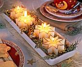 Ungewöhnlicher Adventskranz mit weißen Kerzen in Sternform