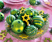 Christmas baubles and wooden stars on glass plate