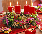 Advent wreath made of mixed green with tree decorations, mistletoes