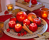 Apples as tealight holder on metal dish