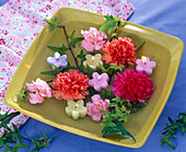 Flowers of Dianthus, Hedera, floating candles in flower form