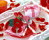 Rose decorated with red felt hearts, on checkered napkin