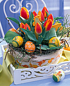 Easter basket with Tulipa, Easter eggs and chicken plug on white tray
