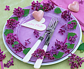 Syringa flowers on purple glass plate, white plate as place indicator, heart with message