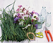 Bouquets in bottles on grass coat