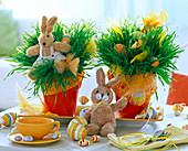 Triticum in light red pots with Easter eggs and stuffed bunnies