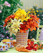 Bouquet of Lilium in yellow, red and orange in checkered vase