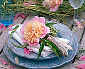 Paeonia blossoms with hay on white cloth napkin, cutlery
