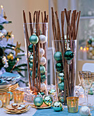 Cinnamon sticks in tall glasses with green and cream colored balls