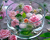 Pink flowers of roses, clematis, white floating candles