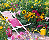 Folding deck chair on the flowering bed with Rudbeckia fulgida and hirta