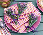 Bouquets with lavandula on checkered napkins on pink