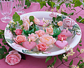 Flowers of pink rose, clematis, heart-shaped floating candles