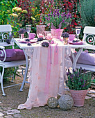 Lavandula in pink coffins in front of and on white table, chairs