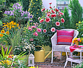 Terrace with dahlias, lily and wicker furniture
