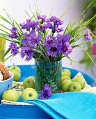 Strauß aus Centaurea (Kornblumen) und Gräsern in blau gestreifter Vase