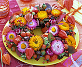 Autumn wreath with berries, fruits, leaves and flowers