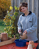 Woman cleaning clay pots with brush and water